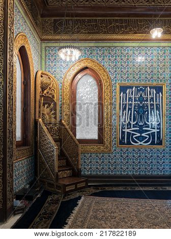 Cairo, Egypt - December 2, 2017: Golden ornate minbar wooden arched window framed by golden ornate floral pattern and floral blue pattern ceramic tiles wall at the public mosque of Manial Palace of Prince Mohammed Ali