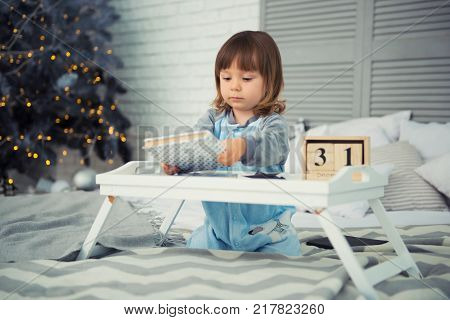 Emotional smiling little girl sitting in pajama with Christmas gifts near New Year's tree and playing snowballs.