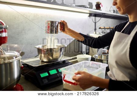A woman sifts the flour through a sieve in the kitchen.