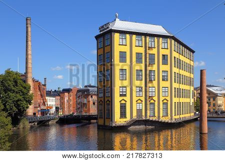 Norrkoping Sweden - July 4 2014: The Industrial Landscape with the Strykjarnet (Ironworks the yellow building) in the River Motala To the right of the building in the water is the sculpture
