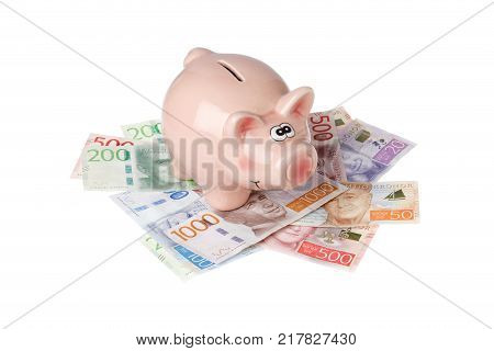 Stockholm Sweden - December 16 2016: One pink piggy bank on Swedish banknotes isolated on white background.
