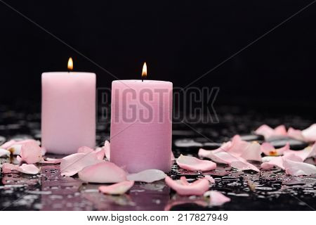 Still life with pink rose petals with two candle and therapy stones