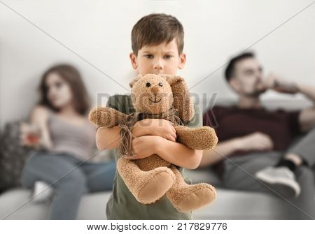 Upset little boy hugging toy bunny while his parents drinking alcohol on background