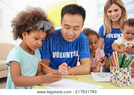 Young male volunteer drawing with little children at table. Volunteering abroad concept