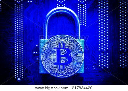 Bitcoin with padlock on computer motherboard. Crypto currency Internet data privacy information security concept. Blue toned image.