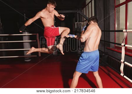Young professional kickboxers training in ring