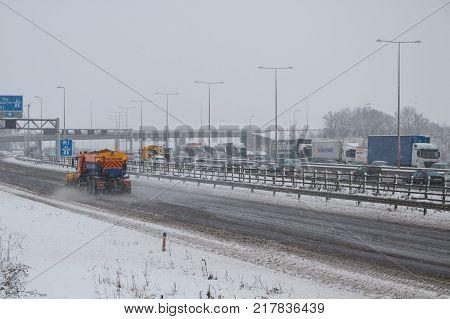 Hemel Hempstead UK - December 10 2017: Snow plough truck spreading salt on the british motorway m1 during snowstorm