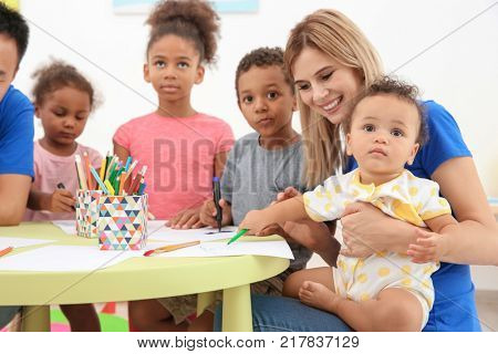 Young female volunteer drawing with little children at table. Volunteering abroad concept
