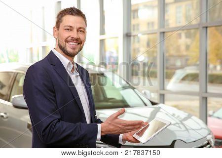 Handsome car salesman with tablet computer in dealership centre