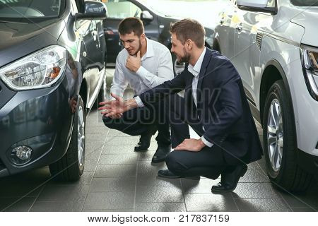 Handsome car salesman with trainee looking at automobile in dealership centre