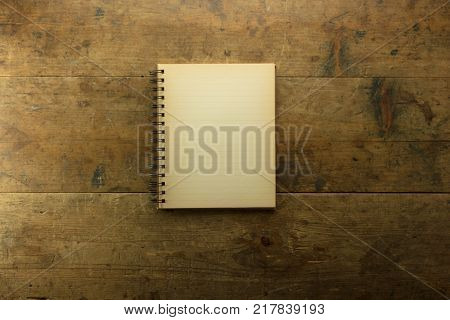 Old blank notebook, open on an rustic or authentic old wooden table with plenty of copy space.