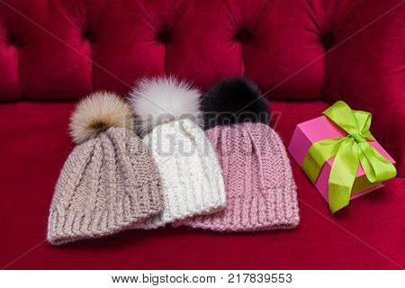 winter knitted hats with a fur ball lay on the red couch. knitted hats and a New Year's gift