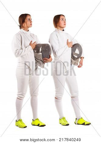 Two beautiful young fencer girls dressed in a fencing uniform, holding a mask for fencing, holding a hand on their hearts and looking up. Isolated on white background.