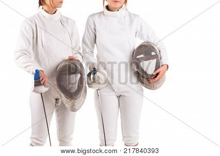 Two girl fencers, dressed in a fencing uniform, hold a special fencing mask in their hands, standing close to each other. Isolated on white background.