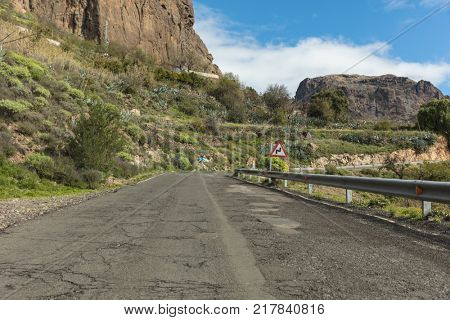 Street with broket sphalt and curve in Gran Canaria road with double curve road sign