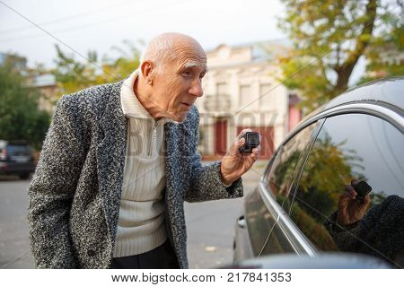The old gray-haired man is standing on the street, holding a small action camera in his hand and looking in the tinted window of the car. Outdoors on the street.