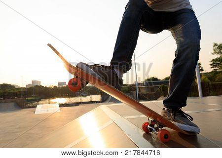closeup of skateboarder legs skateboarding on skatepark