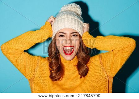 Portrait of a smiling young girl dressed in winter clothes looking at camera isolated over blue background