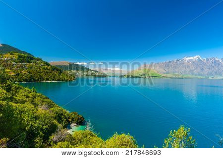 Beautiful blue lake Wakatipu near Queenstown with mighty Southern Alps mountains on horizon. Otago region, New Zealand.