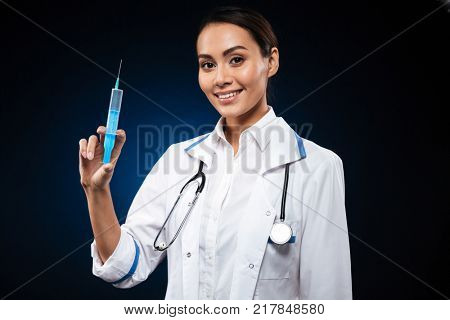 Smiling lady doctor with stethoscope holding syringe and looking camera isolated over black