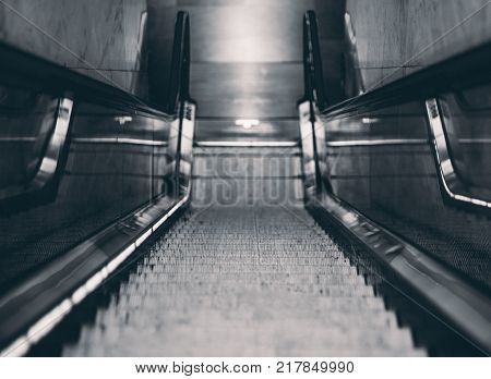 Shallow depth of field shooting from center of descending metro moving stairway; view from above of empty glass and chrome escalator going down to exit from train station in dark urban interior