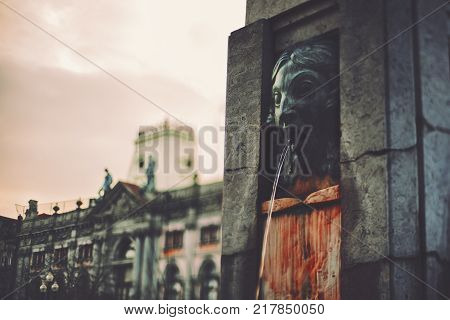 Dark moody true tilt-shift view of fountain in the center of Porto Portugal with evil angry head belching water from mouth bloody marble pedestal and historical building in background behind