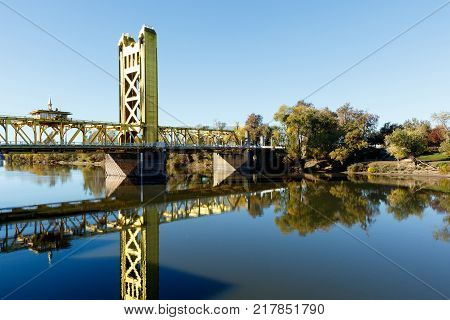 Yellow painted Tower Bridge across the Sacramento River, California; reflection of the structure is visible in the calm, blue water