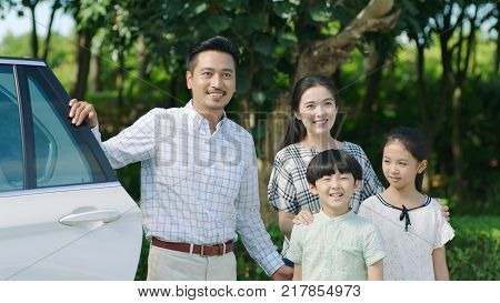 portrait of Chinese parents and kids standing outdoors beside car and smiling