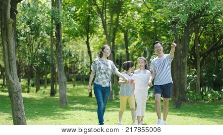 Chinese family smiling & walking together in park while father pointing to the distance
