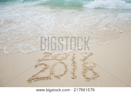 2017 is going end of year and Happy new year 2018 written on sand beach with blue wave New Year 2018 is coming concept.