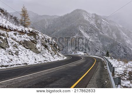 Scenic view of the hairpin bend winding road through the pass part of a mountain serpentine in the autumn cloudy weather with snow