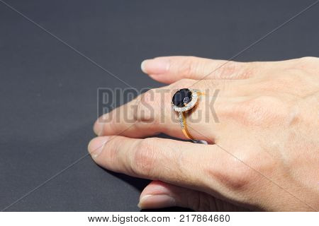 Hand female wears a black diamond ring with middle finger a diamond on black background.