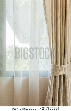 Beige curtain by the window in bed room.