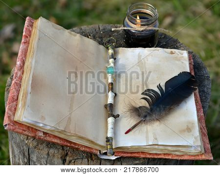 Old book with empty pages, magic wand, quill and black candle. Occult, esoteric, divination and wicca concept, mystic background