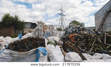 On the territory of the recycling plant, large heaps of plastic canisters and boxes, ecology concept