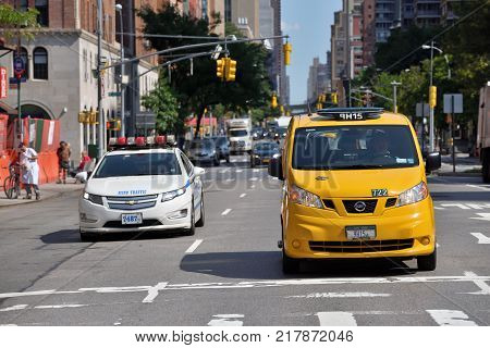 NEW YORK CITY USA - AUG. 26: Yellow taxis and police car on street in Manhattan on August 26 2017 in New York City NY. Manhattan is the most densely populated borough of New York City.