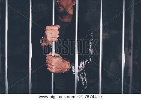 Handcuffed man behind prison bars. Arrested criminal male person imprisoned.