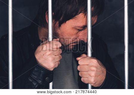Man behind prison bars. Arrested criminal male person imprisoned.