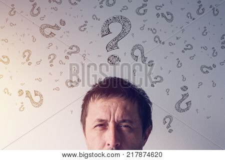 Question mark looking for answers. Perplexed man with scribbled interrogation point symboles around his head.