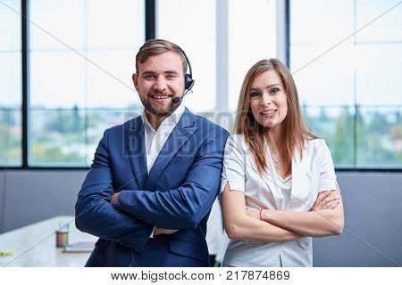Close-up of a young girl and a man are standing in the office with arms folded near the chest, the man in the ear has an earpiece with a microphone, call center employees, look at the camera.