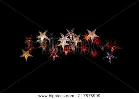Colorful paper stars isolated on black margin Christmas holidays winter New Years background texture