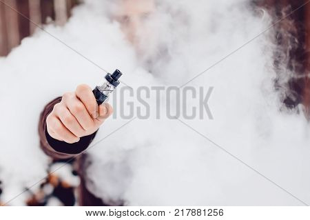 Vape. Man in the smoke holds an electronic device vape