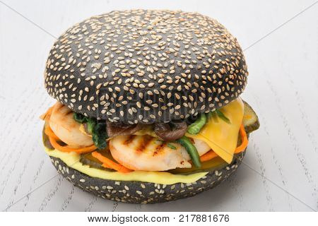 Black burger with chicken grill, pickle, spinach cheese. bun is strewed with sesame seeds over white wooden background