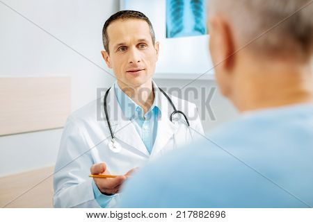 Doctor and patient. Serious experienced female doctor looking at his patient and holding his notebook while being ready to write