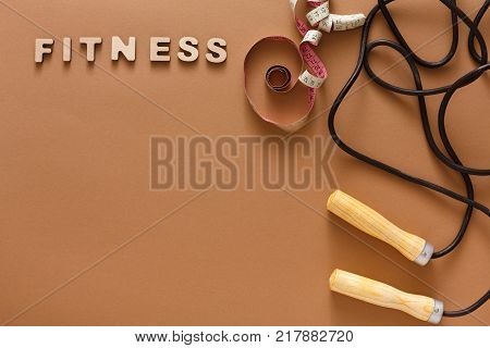 Fitness word, jumping rope and measuring tape on brown background. Skipping rope, sport supply, weightloss, slimming concept