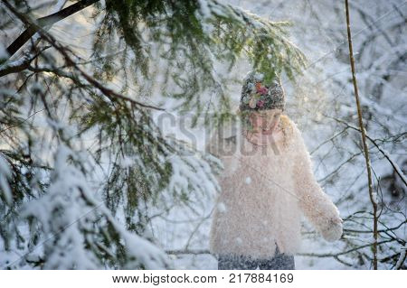 The girl of 8-9 years to shake on herself snow from a fir-tree. Walk in the winter wood. Pleasure for the child.