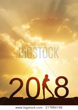 Happy new year card 2018.Silhouette of healthy young woman standing on land watching sunset or sunrise sky background.Happy joyful girl looking the rising sun stand as a part of the Number 2018 sign.