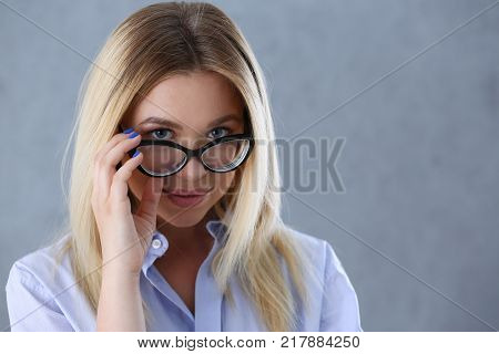Portrait of a sexy woman in a man's shirt wearing glasses on a gray background looks at the camera and smiling look advice to give wants objections are not accepted.