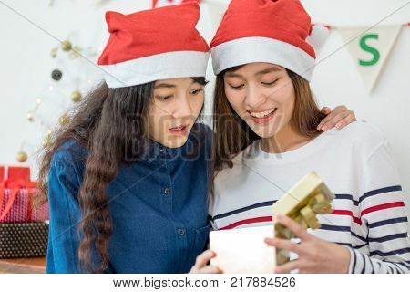 Two asia woman surprise when open gold gift box at holiday party with decoration flag at backgroundgiving Christmas party presentwow feeling and happiness moment lesbian lgbt couple lifestyle