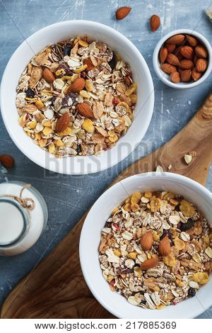 The almond milk in the glass bottle with almond nuts in the white bowl on the wooden decorative rustic cutting board.